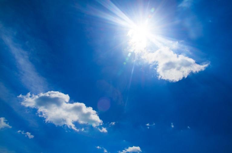 Bright sun shining against deep blue sky