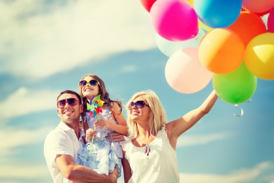 A family enjoying summer; they hold balloons but look away from them.