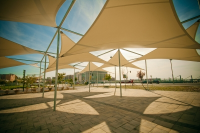 Multiple shade sails creating a pattern of shade and light on the earth beneath them.
